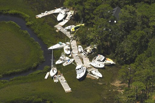 In this aerial photo boats and docks are washed together along the marsh near Southport, N.C. as Tropical Storm Isaias came ashore Tuesday night Aug. 4, 2020 in Brunswick County. The storm caused damage along all of the southern beaches like Ocean Isle Beach, Holden Beach, Oak Island and Southport. (Ken Blevins/Wilmington Star-News via AP)