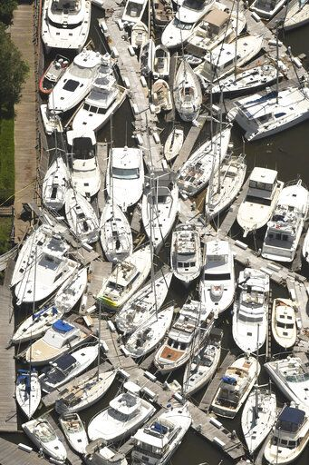 In this aerial photo boats are stacked on top of each other in the Southport Marina Tuesday Aug. 4, 2020 in Southport N.C. after Tropical Storm Isaias came ashore over night in Brunswick County. (Ken Blevins/Wilmington Star-News via AP)