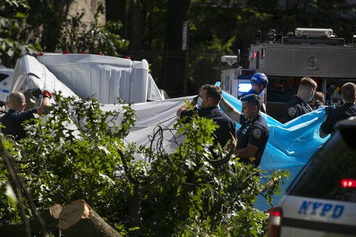 New York City Police officers shield a person from view who died after a tree fell on a van as Tropical Storm Isaias moved past New York, Tuesday, Aug. 4, 2020, in New York.
