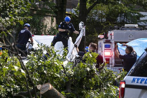 New York City Police and Parks employees work to remove a person who died when a tree fell on a van as Tropical Storm Isaias moved past New York Tuesday, Aug. 4, 2020, in New York.
