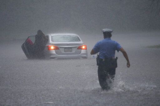 A Philadelphia police officer rushes to help a stranded motorist during Tropical Storm Isaias, Tuesday, Aug. 4, 2020, in Philadelphia. The storm spawned tornadoes and dumped rain during an inland march up the U.S. East Coast after making landfall as a hurricane along the North Carolina coast.