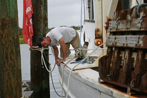 Royce Potter, a fifth generation seafood farmer, suveys the damage to his fishing vessel following the effects of Hurricane Isaias in Southport, N.C., Tuesday, Aug. 4, 2020. Potter spent the night on his docked boat.