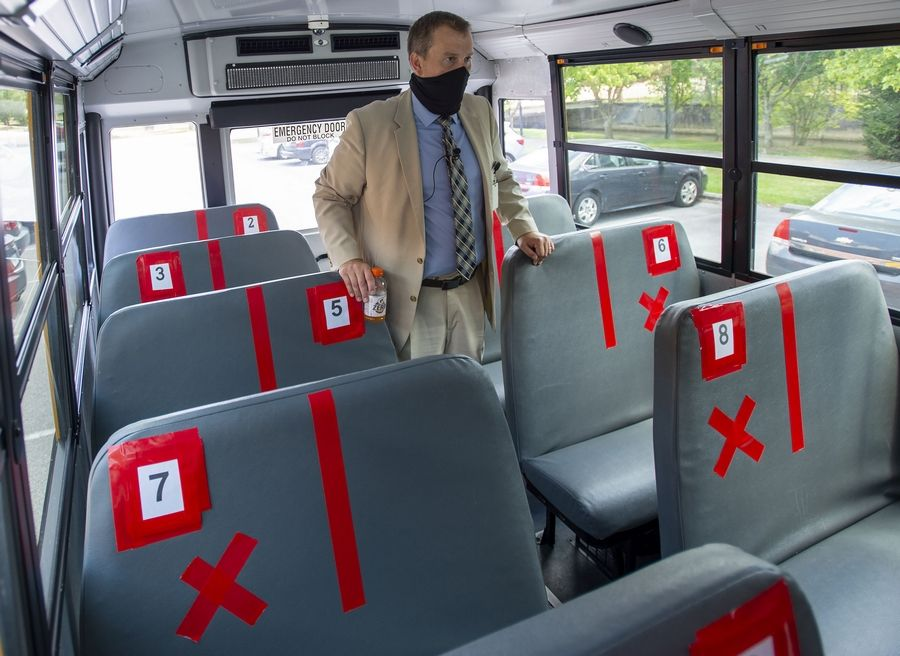 In this Thursday, July 16, 2020, file photo, Superintendent Keith Perrigan shows the new seating configuration on the school buses for the upcoming school year, in Bristol, Va., where a maximum of 22 students can be on the bus, amid the coronavirus pandemic. (David Crigger/Bristol Herald Courier via AP, File)