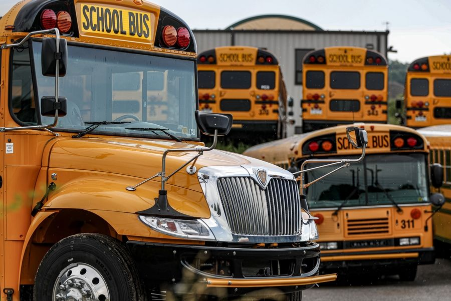 In this Friday, July 10, 2020, file photo, rows of school buses are parked at their terminal, in Zelienople, Pa. Reopening schools during the coronavirus pandemic means putting children on school buses, and districts are working on plans to limit the risk.