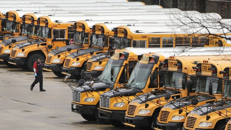 In this April 27, 2020, file photo, a worker passes public school buses parked at a depot in Manchester, N.H. Reopening schools during the coronavirus pandemic means putting children on school buses, and districts are working on plans to limit the risk.