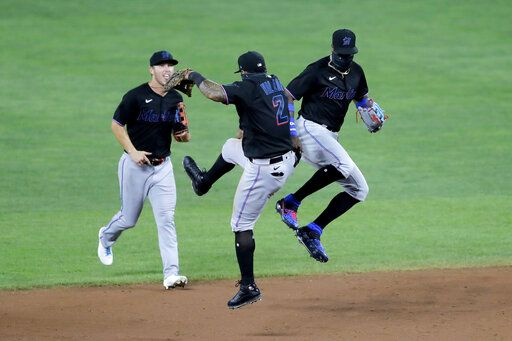 Miami Marlins shortstop Jonathan Villar (2) and center fielder Monte Harrison, right, celebrate after defeating the Baltimore Orioles 2-1 in the second game of a doubleheader, Wednesday, Aug. 5, 2020, in Baltimore. Marlins' Corey Dickerson, left, looks on.