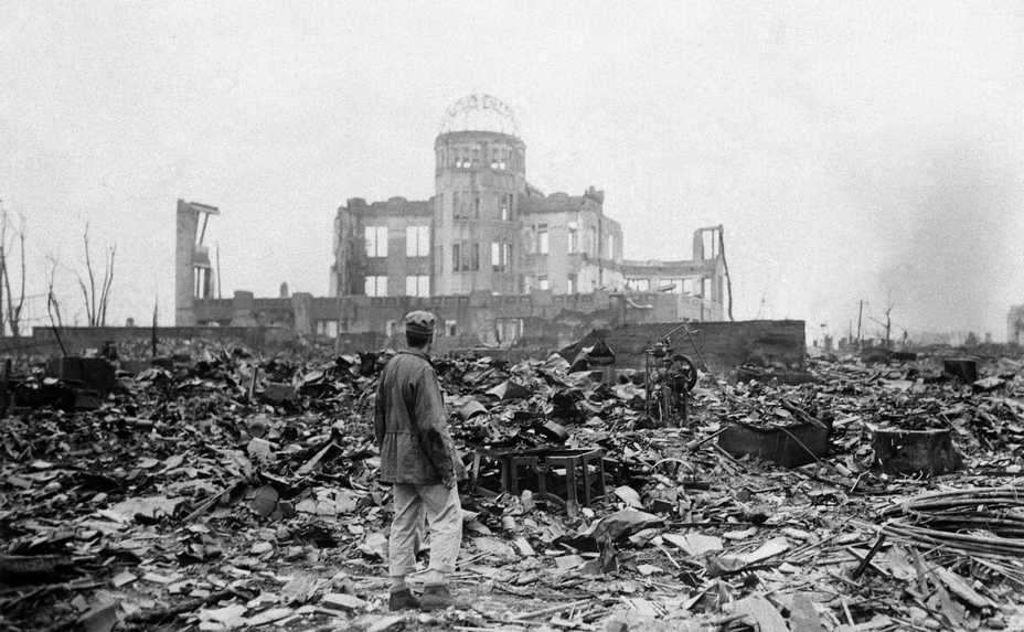 An Allied correspondent stands in front of the shell of a movie theater in Hiroshima, Japan, a month after the U.S. dropped an atomic bomb.