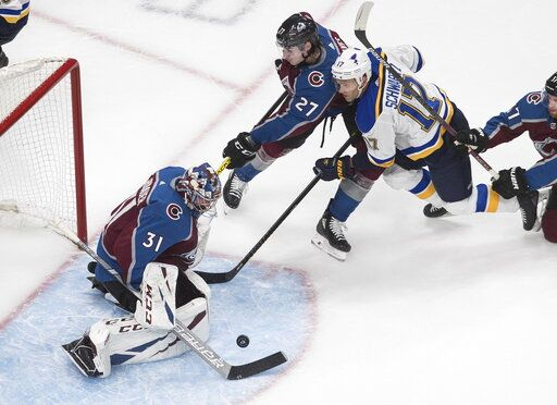 Colorado Avalanche goalie Philipp Grubauer (31) makes a save on St. Louis Blues' Jaden Schwartz (17) as Ryan Graves (27) defends during the third period of an NHL hockey playoff game Sunday, Aug. 2, 2020, in Edmonton, Alberta. (Jason Franson/The Canadian Press via AP)