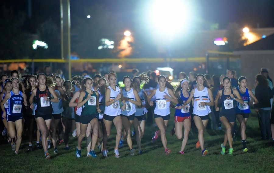 The girls varsity race starts under the lights at last year's Twilight cross country invitational Wednesday at Naperville North High School. There won't be this many runners at the starting line in this fall's races.