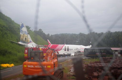 The Air India Express flight that skidded off a runway while landing at the airport in Kozhikode, Kerala state, India, Saturday, Aug. 8, 2020. The special evacuation flight bringing people home to India who had been trapped abroad because of the coronavirus skidded off the runway and split in two while landing in heavy rain killing more than a dozen people and injuring dozens more.