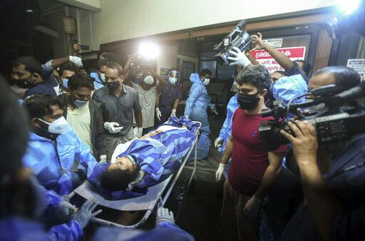 One of the persons injured after an Air India Express flight skidded off a runway while landing at the Kozhikode airport is brought for treatment to the Medical College Hospital in Kozhikode, Kerala state, India, Friday, Aug. 7, 2020.