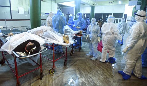 Medical personnel in personal protective wear stand next to bodies of victims after an Air India Express flight skidded off a runway while landing at the Kozhikode airport iare attended to at the Medical College Hospital in Kozhikode, Kerala state, India, Friday, Aug. 7, 2020.