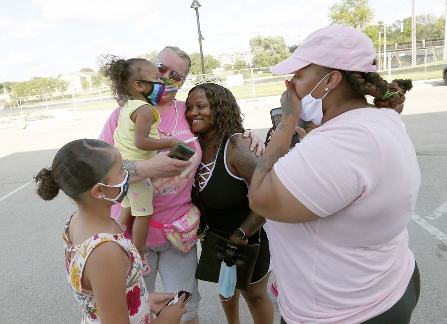 Fiona Galvin, center in pink, is surrounded by friends and family Saturday at a rally for her daughter Kianna Galvin, the South Elgin teen who disappeared four years ago.