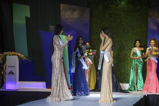 Ana Marcelo, an agroindustrial engineer from the city of Esteli, center right, reacts after being chosen Miss Nicaragua, in Managua, Nicaragua, Saturday, Aug. 8, 2020. Marcelo was crowned in front of a limited audience (two people per contestant spaced safely) plus a production crew of 85. The masks were off the contestants, but the judges wore them and were spaced at a safe distance.