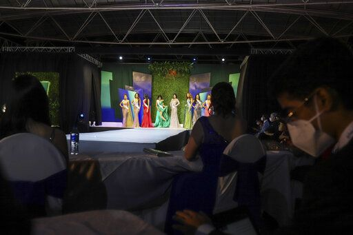 Attendees watch the Miss Nicaragua pageant, in Managua, Nicaragua, Saturday, Aug. 8, 2020. The limited audience consisted of two people per contestant spaced safely, plus a production crew of 85. The masks were off the contestants, but the judges wore them and were spaced at a safe distance.