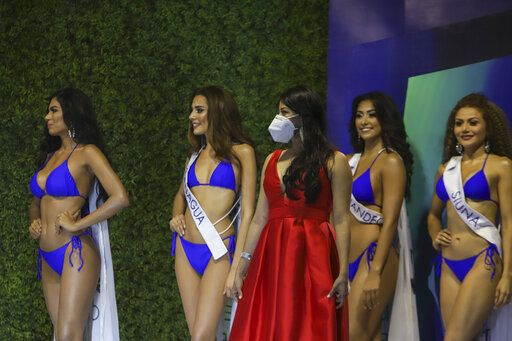 Contestants wait on the side of the stage of the Miss Nicaragua pageant, in Managua, Nicaragua, Saturday, Aug. 8, 2020. The limited audience consisted of two people per contestant spaced safely, plus a production crew of 85. The masks were off the contestants, but the judges wore them and were spaced at a safe distance.