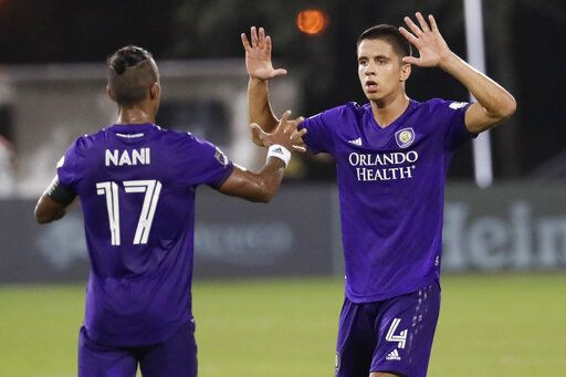Orlando City defender Joao Moutinho (4) celebrates a goal with teammate Orlando City forward Nani (17) during the second half of an MLS soccer match, Friday, July 31, 2020, in Orlando, Fla.