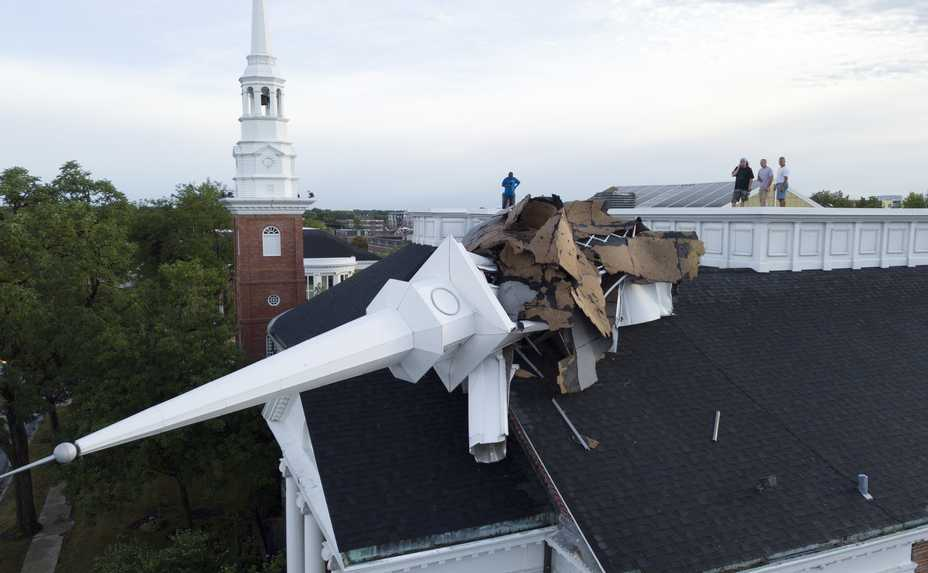 The steeple at College Church in Wheaton collapsed during Monday's derecho. Here, officials check out the damage from the rooftop.