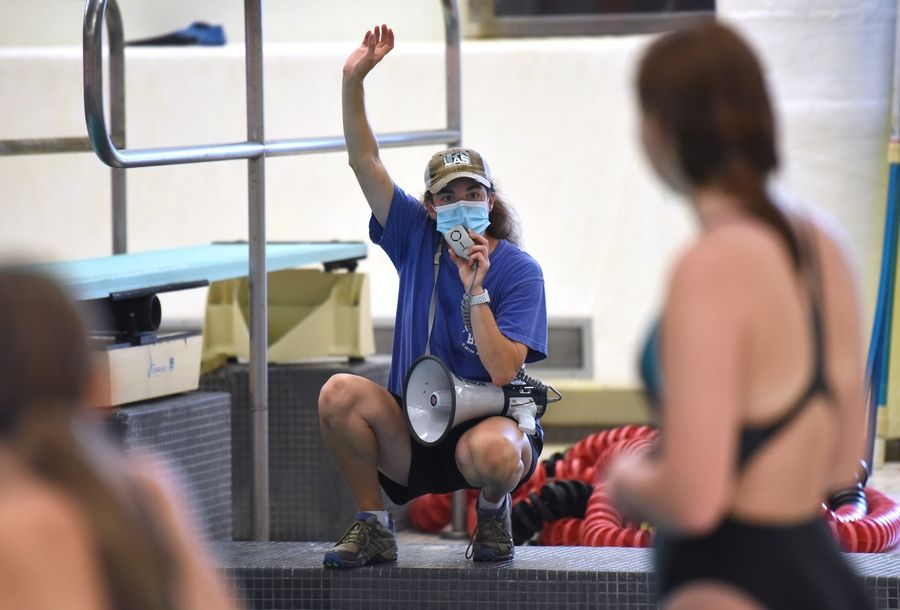 Barrington High School diving coach Lisa Christianson uses a megaphone so divers can hear instructions through her mask during first day of practice Monday at the school.