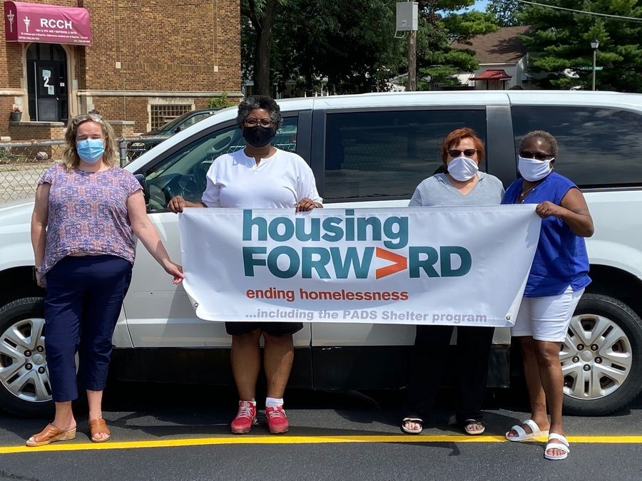 Housing Forward staff show the vehicle donation provided by National Express Transit.