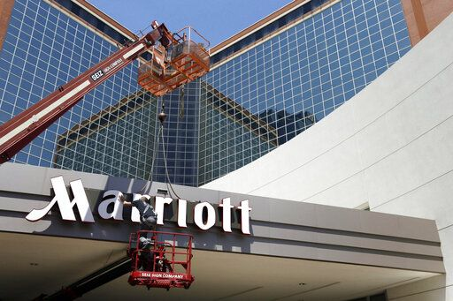 FILE - In this Tuesday, April 30, 2013, file photo, a man works on a new Marriott sign in front of the former Peabody Hotel in Little Rock, Ark. Marriott says its business is steadily improving, Monday, Aug. 10, 2020, with 91% of its hotels now reopen and business travel reemerging in China.
