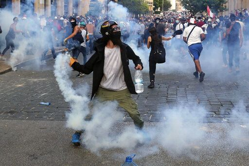 Protesters throw back tear gas canisters towards riot policemen during an anti-government protest, in the aftermath of last Tuesday's massive explosion which devastated Beirut, Lebanon, Monday, Aug. 10, 2020.