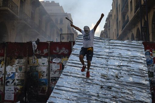 A man jumps from a barrier blocking the access to the parliament building during an anti-government protest, in the aftermath of last Tuesday's massive explosion which devastated Beirut, Lebanon, Monday, Aug. 10, 2020.