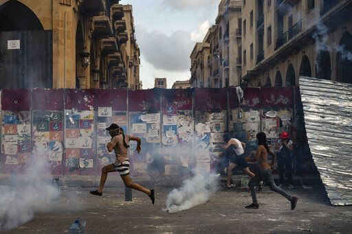 Demonstrators run from tear gas fired by police near the parliament building during an anti-government protest, following last Tuesday's massive explosion which devastated Beirut, Lebanon, Monday, Aug. 10, 2020.
