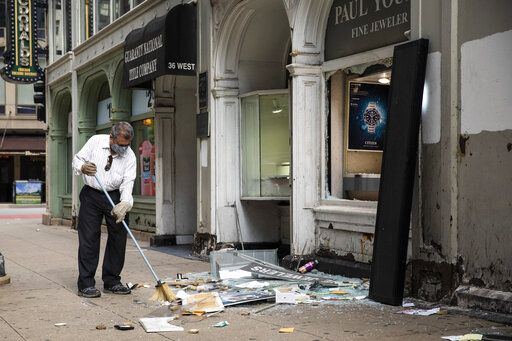 A man sweeps up outside Paul Young Fine Jewelers after looting broke out in the Loop and surrounding neighborhoods overnight, Monday morning, Aug. 10, 2020 in Chicago. Police Superintendent David Brown says when police shot a man who opened fire on officers Sunday, the incident apparently prompted a social media post urging looters to converge on the business district.  (Ashlee Rezin Garcia /Chicago Sun-Times via AP)