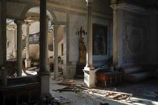 Broken glass and window frames lay on the floor of the Sursock Palace, heavily damaged after the explosion in the seaport of Beirut, Lebanon, Friday, Aug. 7, 2020. The level of destruction from the massive explosion at Beirut's port last week is ten times worse than what 15 years of civil war did. (AP Photo/Felipe Dana)