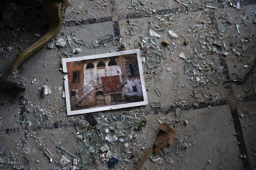 A photo rests among broken glass on the floor of the Sursock Palace, heavily damaged after the explosion in the seaport of Beirut, Lebanon, Friday, Aug. 7, 2020. The Sursock palace, built in 1860 in the heart of historical Beirut on top of a hill overlooking the now-obliterated port, is home to beautiful works of arts, Ottoman-era furniture, marble and paintings from Italy - the result of more than three long-lasting generations of the Sursock family.