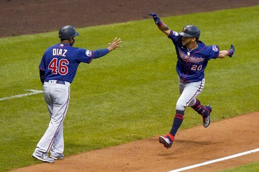 Minnesota Twins' Eddie Rosario celebrates his grand slam with third base coach Tony Diaz during the third inning of a baseball game against the Milwaukee Brewers Monday, Aug. 10, 2020, in Milwaukee.