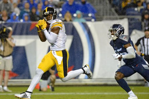 FILE - In this Aug. 25, 2019, file photo, Pittsburgh Steelers wide receiver JuJu Smith-Schuster catches a 17-yard touchdown pass ahead of Tennessee Titans cornerback LeShaun Sims (36) in the first half of a preseason NFL football game in Nashville, Tenn. Smith-Schuster is looking for a big bounce-back this season.