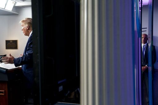 A member of the Secret Service stands guard, right, as President Donald Trump, left, speaks at a news conference in the James Brady Press Briefing Room at the White House, Monday, Aug. 10, 2020, in Washington. Trump briefly left because of a security incident outside the fence of the White House.