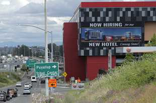 "A large video display reads ""Now hiring for our new hotel coming soon!,"" at the new Emerald Queen Casino, which is open, and owned by the Puyallup Tribe of Indians, in Tacoma, Washinging. The United States added 1.8 million jobs in July, a pullback from the gains of May and June and evidence that the resurgent coronavirus has weakened hiring and the economic rebound."