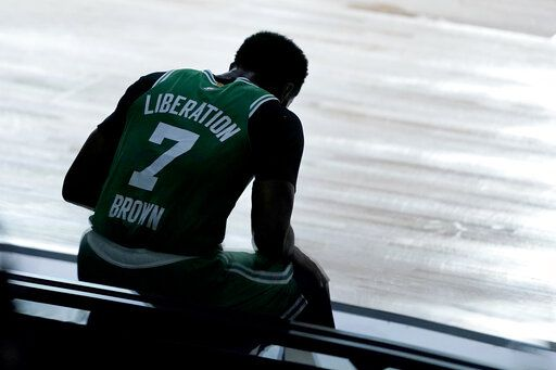 Boston Celtics' Jaylen Brown sits on a side board after committing a foul against the Toronto Raptors during the first half of an NBA basketball game Friday, Aug. 7, 2020 in Lake Buena Vista, Fla.