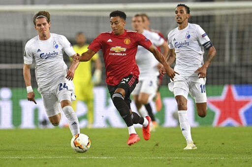 Manchester United's Jesse Lindgard, center, controls the ball as Copenhagen's Robert Mudrazija, left, and Zeca try to stop him during the Europa League quarter-final soccer match between Manchester United and Copenhagen at the Rhein Energie Stadium in Cologne, Germany, Monday, Aug. 10, 2020. (Sascha Steinbach/Pool via AP)