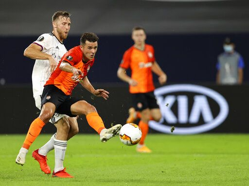 Shakhtar Donetsk's Junior Moraes, front, duels for the ball with FC Basel's Silvan Widmer during the Europa League quarter finals soccer match between FC Shakhtar Donetsk and FC Basel at the Veltins-Arena in Gelsenkirchen, Germany, Tuesday, Aug. 11, 2020. (Wolgang Rattay/Pool Photo via AP)