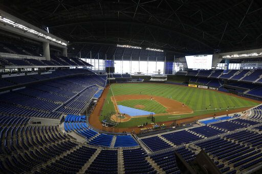 FILE - This is a July 4, 2020, file photo showing the Miami Marlins running drills during a baseball workout at Marlins Park in Miami. Marlins Park will have a new look for its 2020 season debut Friday, thanks to cozier dimensions and a switch to artificial turf. Also, the home team is in first place.