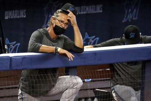 FILE - In this Sunday, July 12, 2020, file photo, Miami Marlins manager Don Mattingly watches a baseball scrimmage at Marlins Park in Miami. Marlins Park will have a new look for its 2020 season debut Friday, Aug. 14, 2020, thanks to cozier dimensions and a switch to artificial turf. Also, the home team is in first place.
