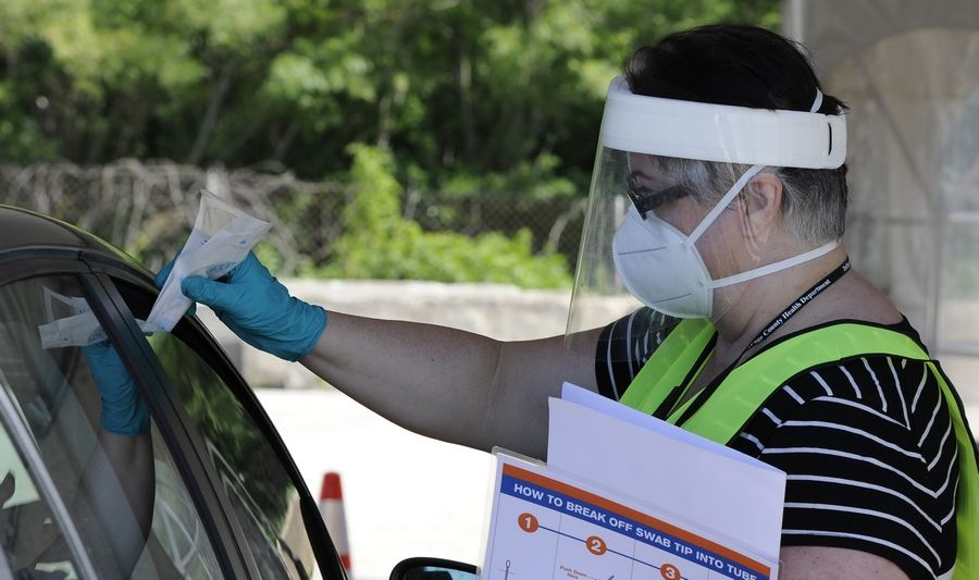 Sample instructor Kimberly Morgan of Chicago hands a test kit through a window to a test subject at the DuPage County COVID-19 testing site in Wheaton in June.
