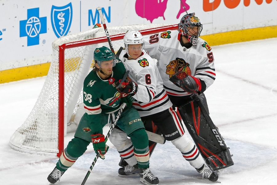 Chicago Blackhawks' Olli Maatta, center, of Finland, keeps Minnesota Wild's Ryan Hartman in check as goalie Corey Crawford defends the net in the first period of an NHL hockey game Tuesday, Feb. 4, 2020, in St. Paul, Minn.