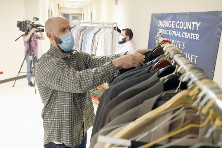 DuPage County jail detainee Gregory Fischer looks through some of the clothes that Naperville-based nonprofit Suits for Success donated for detainees to wear when they are released, have a job interview or go to court.