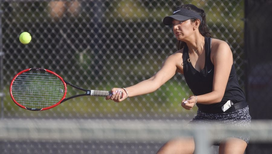 St. Charles East's first singles player Emaira Saini returns a forehand against Geneva's Rachel King Saturday in St. Charles.