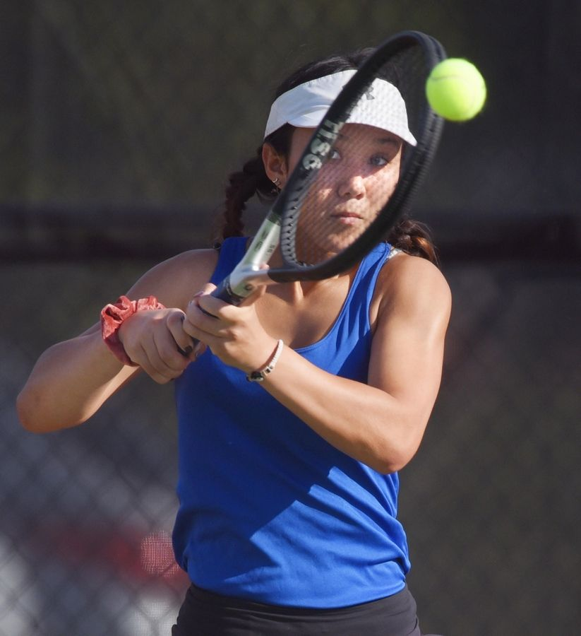 Geneva's first singles player Rachel King returns a shot against St. Charles East's Emaira Saini Saturday in St. Charles.
