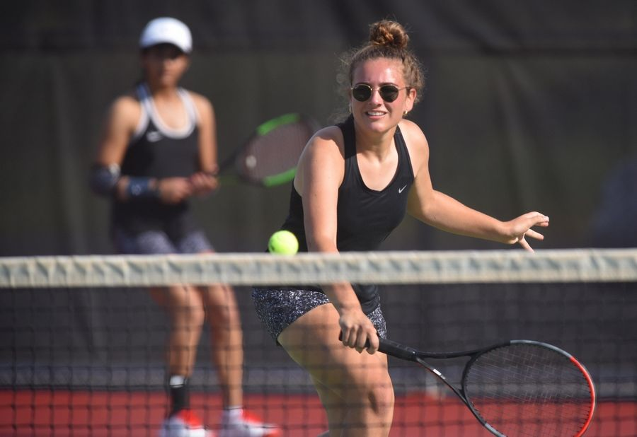 St. Charles East's second doubles player Caroline Donati returns a backhand as partner Smita Dhar watches against Geneva's Karolina Schubert and Julie Drew Saturday in St. Charles.