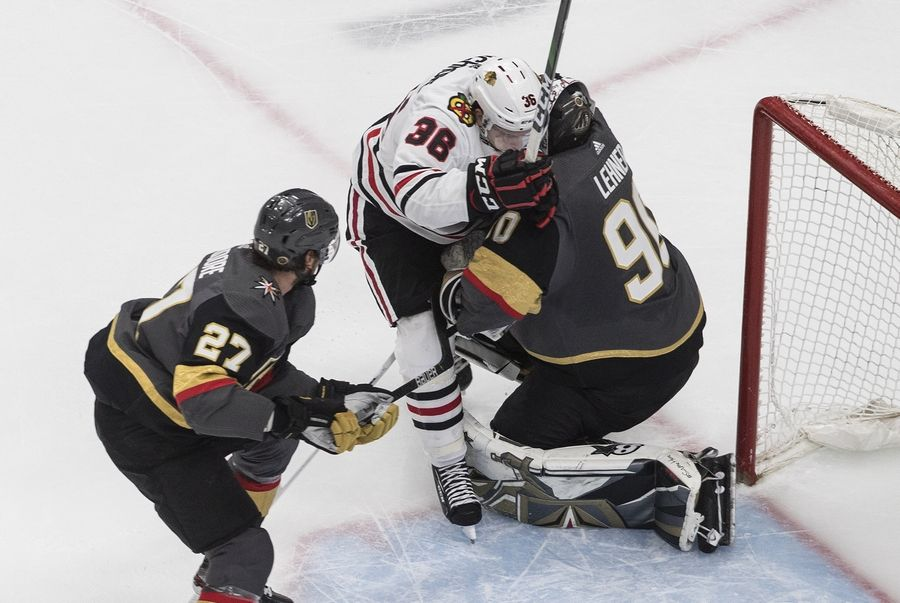 Chicago Blackhawks' Matthew Highmore, left, crashed against Vegas Golden Knights goalie Robin Lehner (90) as Shea Theodore (27) skates in during the second period in Game 5 of an NHL hockey first-round playoff series, Tuesday, Aug. 18, 2020, in Edmonton, Alberta. (Jason Franson/The Canadian Press via AP)