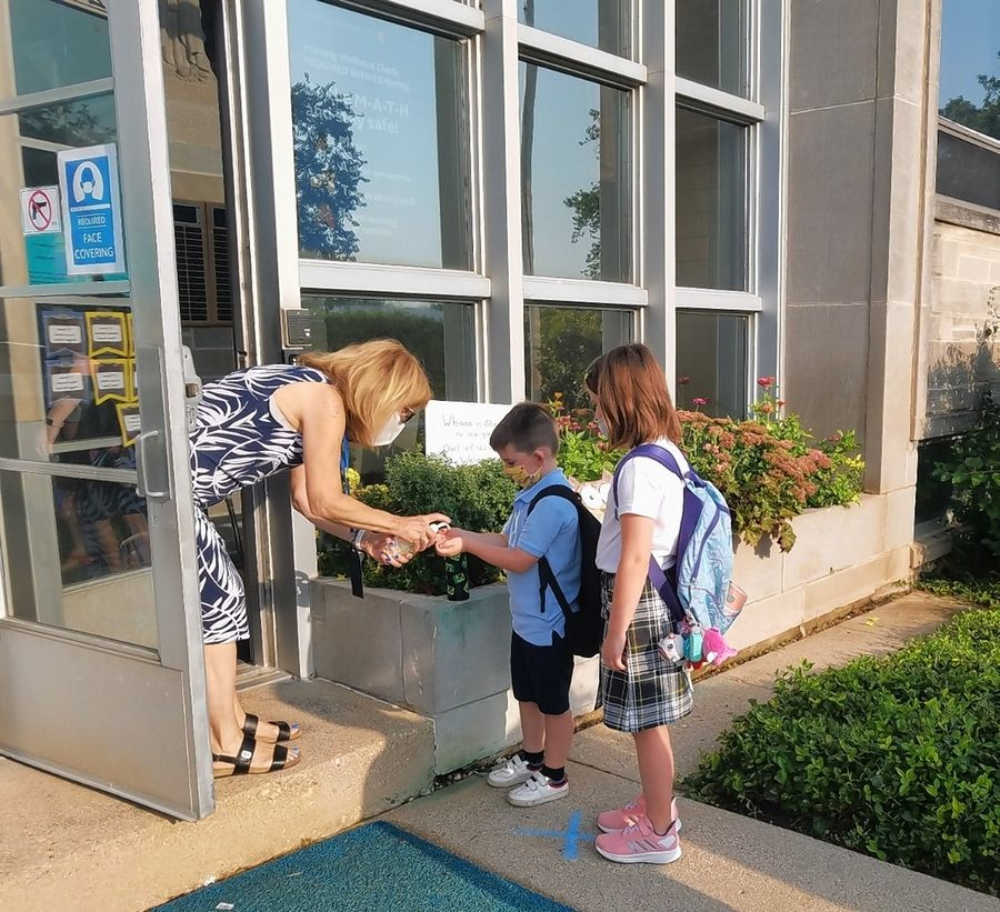 Students received hand sanitizer and a temperature check on their way into Our Lady of the Wayside School in Arlington Heights for the first full day of classes Monday.