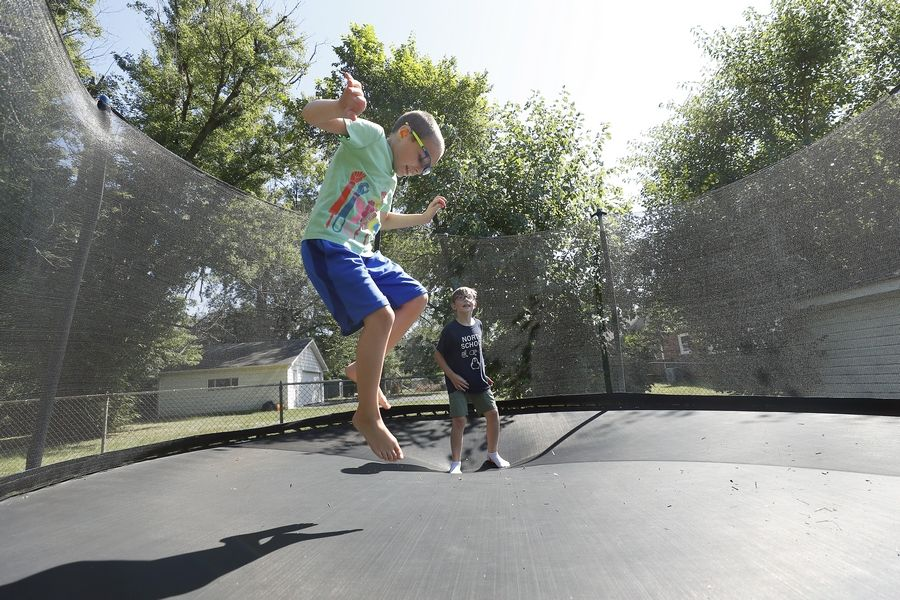 Aidyn Heneghan, 9, rear, and his brother Logan, 7, get rid of some extra energy Thursday. Their mom, Rachel Heneghan, is concerned about districts' reopening plans.