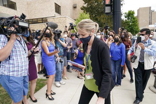 Kasey Morgan, a public information officer for the Lake County Court, walks away from reporters outside the Lake County courthouse following the extradition hearing for Kyle Rittenhouse Friday, Aug. 28, 2020, in Waukegan, Ill. A judge agreed Friday to delay for a month a decision on whether the 17-year-old from Illinois should be returned to Wisconsin to face charges accusing him of fatally shooting two protesters and wounding a third during a night of unrest following the weekend police shooting of Jacob Blake in Kenosha.